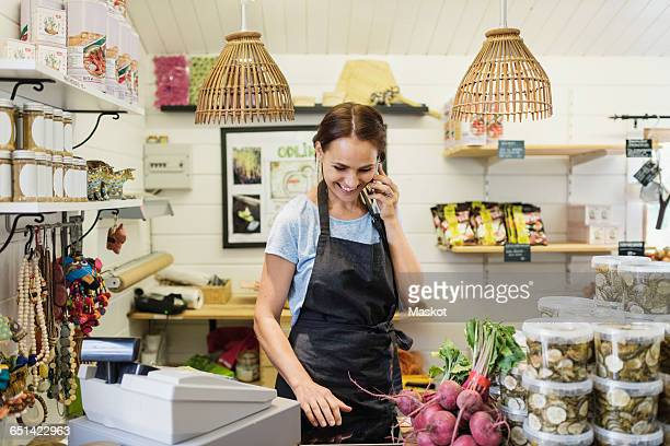 Happy woman talking on mobile phone while standing at counter in store
