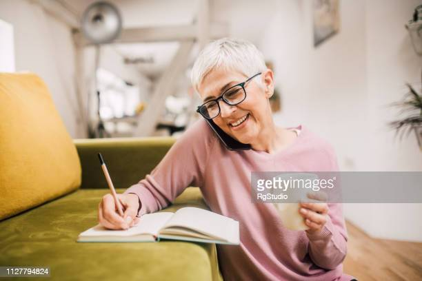 happy woman talking on phone - older woman stock pictures, royalty-free photos & images