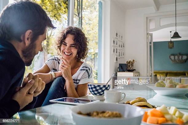 happy woman talking with spouse during breakfast - coppia eterosessuale foto e immagini stock