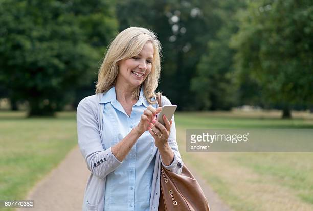 Happy woman text messaging outdoors