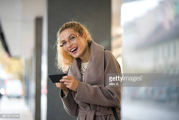 happy woman texting on her mobile phone - avenue stock pictures, royalty-free photos & images