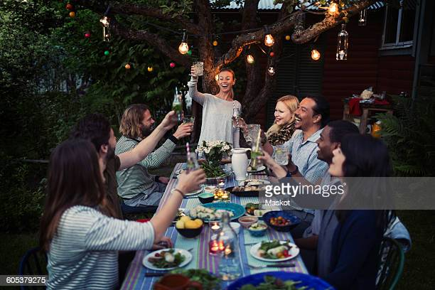Happy woman toasting drink to friends at dining table while enjoying outdoor dinner party