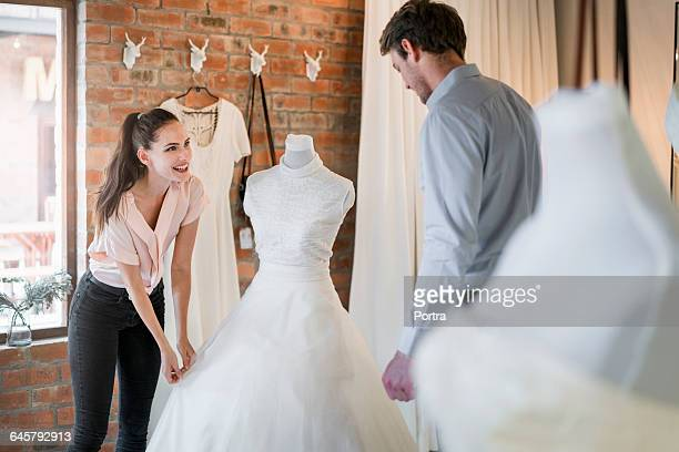 happy woman touching wedding gown in bridal shop - wedding dress stock pictures, royalty-free photos & images