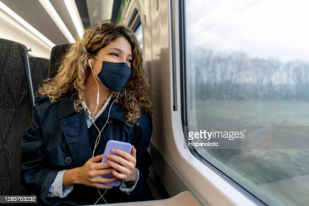 happy woman traveling by train wearing a facemask - uk stock pictures, royalty-free photos & images