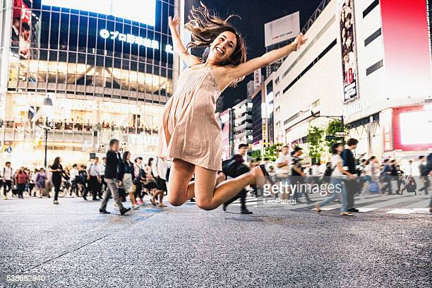 Happy woman travels in Tokyo, Shibuya crossing at night
