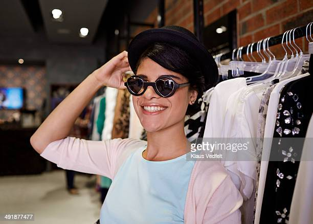 Happy woman trying on crazy sunglasses in shop