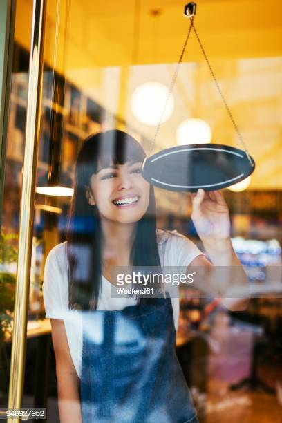 happy woman turning sign in window of a store - cartello chiuso foto e immagini stock