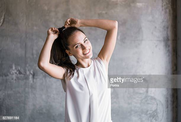 happy woman tying ponytail against concrete wall - ponytail stock pictures, royalty-free photos & images