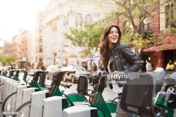 happy woman unlocking bike share on street - green coat stock pictures, royalty-free photos & images