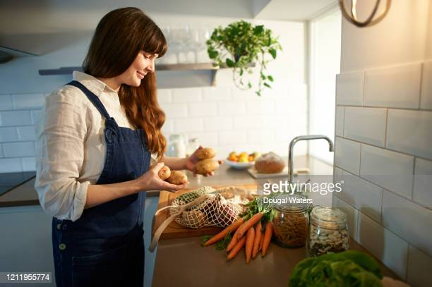 happy woman unpacking shopping from plastic free bag in kitchen. - dieting stock pictures, royalty-free photos & images