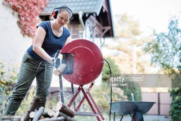 Happy woman using a electric saw cutting wood.