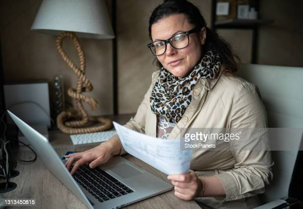 happy woman using computer while working on home finances - economist stock pictures, royalty-free photos & images
