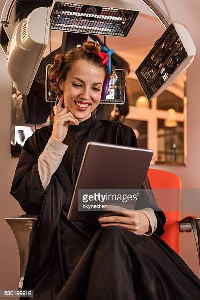 Heureuse femme se servant de tablette numérique sous un sèche-cheveux de coiffeurs.