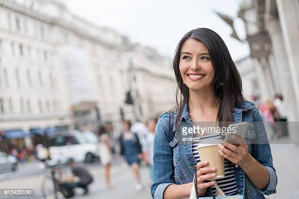 Happy woman using her cell phone outdoors
