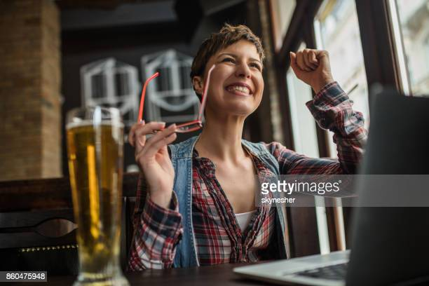 Happy woman using laptop in a bar and celebrating good news.