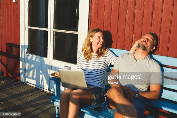 happy woman using laptop while playing with man on bench at porch during summer - surfing the net stock pictures, royalty-free photos & images