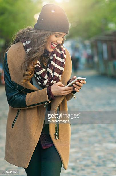 happy woman using mobile phone, - green coat stock pictures, royalty-free photos & images