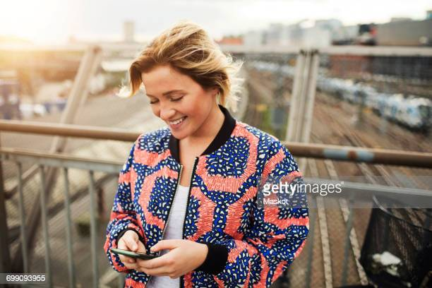 Happy woman using mobile phone while standing on bridge