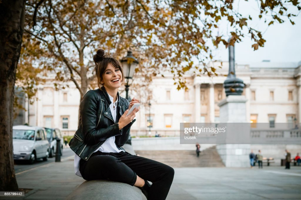 Happy woman using smart phone at Trafalgar Square in London, autumn season : Stock Photo