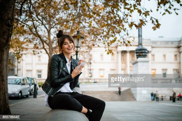 Happy woman using smart phone at Trafalgar Square in London, autumn season