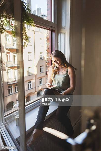 Happy woman using smart phone while holding guidebook on window sill at home