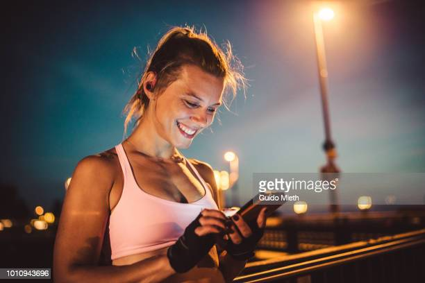 happy woman using smartphone after workout in city. - time of day stock pictures, royalty-free photos & images