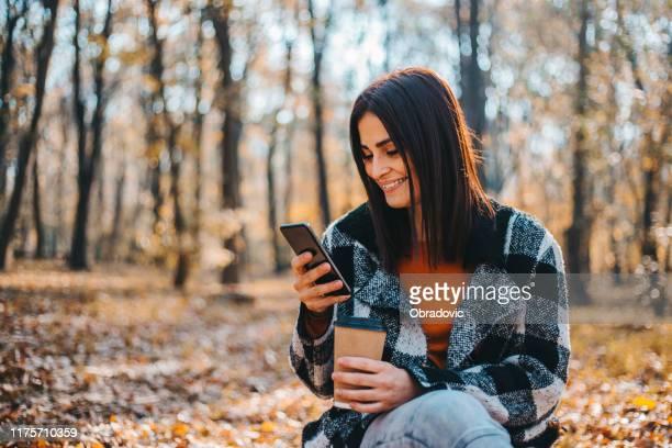 森の美しい秋の日にスマートフォンを使用して幸せな女性 - 十一月 ストックフォトと画像