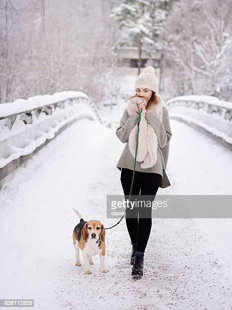 Happy woman walking beagle dog on winter bridge