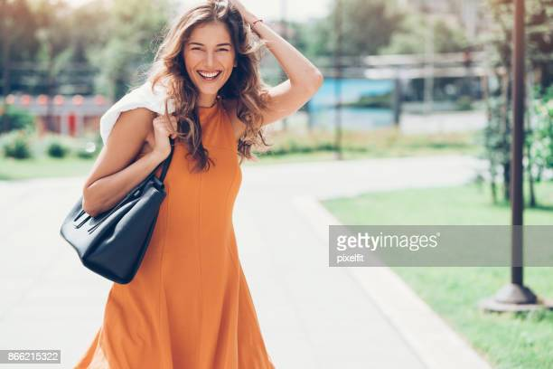 happy woman walking in the city - orange dress stock pictures, royalty-free photos & images