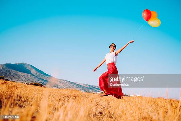 happy woman walking in the field and holding balloons - blue skirt stock pictures, royalty-free photos & images