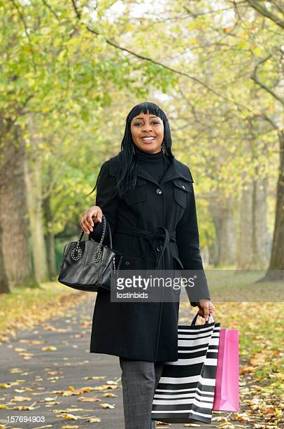 Happy Woman Walking In The Park After A Shopping Spree