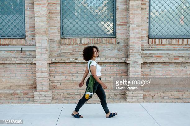 happy woman walking in the street - afro caribbean ethnicity stock pictures, royalty-free photos & images