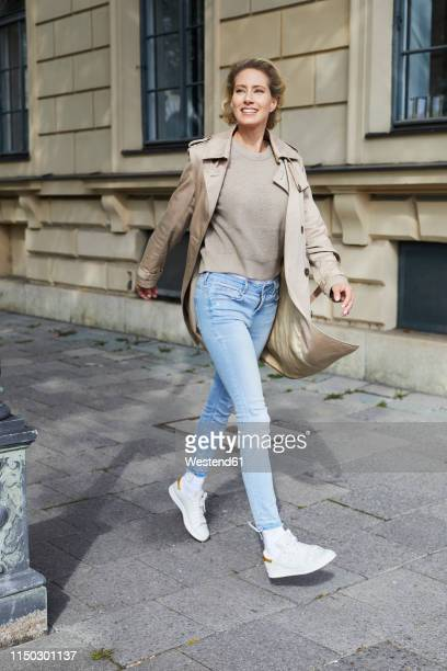 happy woman walking on pavement in the city - coat stockfoto's en -beelden