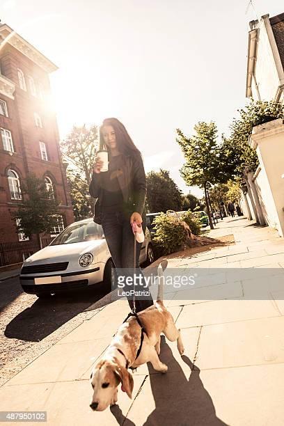 Heureuse Femme marchant avec un chien en tôt le dimanche matin