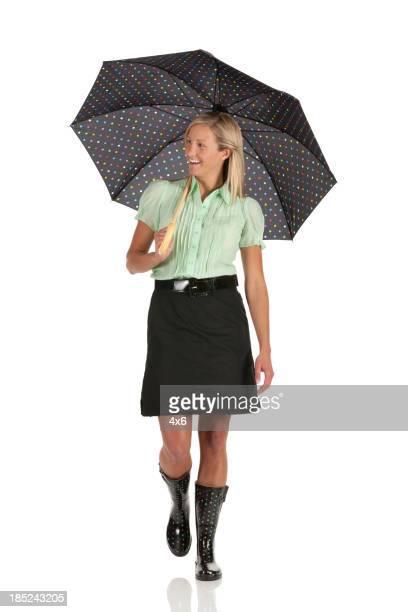 Happy woman walking with umbrella