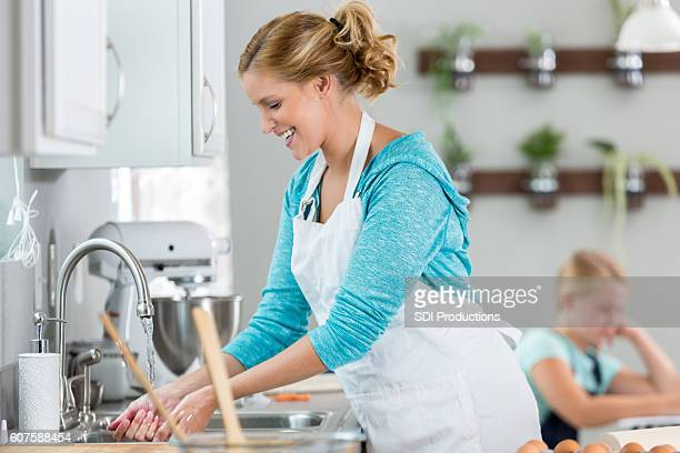 Happy woman washing her hands after baking a pie