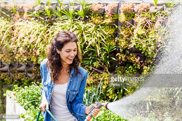 Happy woman watering garden with water hose