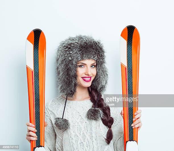 happy woman wearing fur cap holding ski - izusek stock pictures, royalty-free photos & images