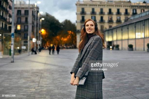 happy woman wearing headphones and holding laptop - long coat stock pictures, royalty-free photos & images