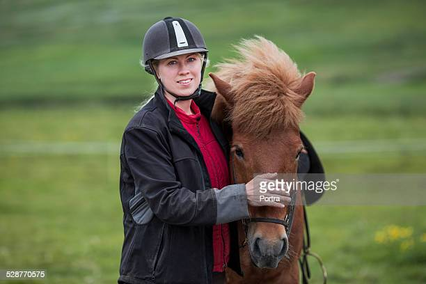Happy woman wearing helmet while stroking horse