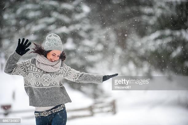 happy woman wearing knitwear dancing in the snow - winter stock-fotos und bilder