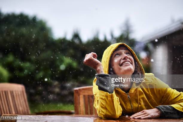 happy woman wearing raincoat during heavy rain in garden - rain stock-fotos und bilder