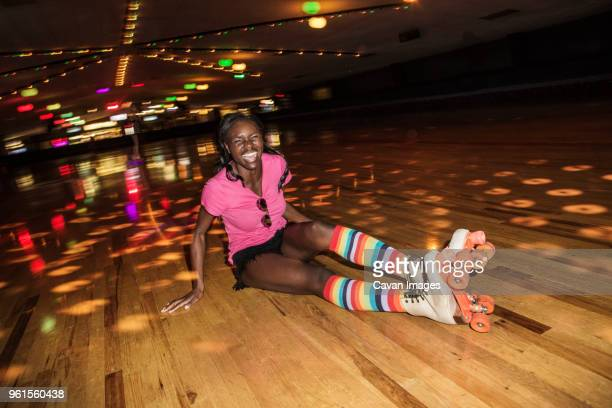 happy woman wearing roller skates sitting at illuminated roller rink - roller rink stock photos and pictures