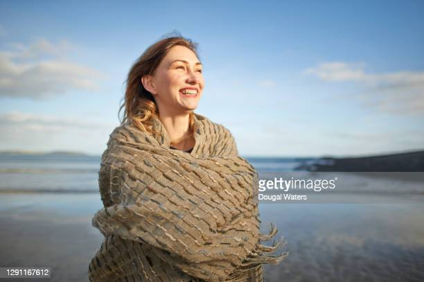 happy woman wearing shawl on autumn beach. - glowing stock pictures, royalty-free photos & images