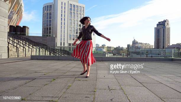 happy woman wearing striped skirt and jacket on footpath in city - 回転する ストックフォトと画像