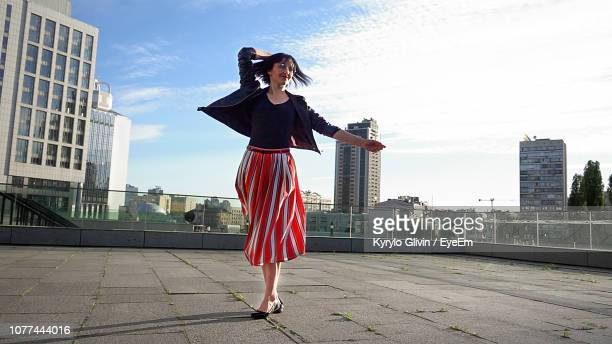 happy woman wearing striped skirt and jacket on footpath in city - ankle length stock pictures, royalty-free photos & images