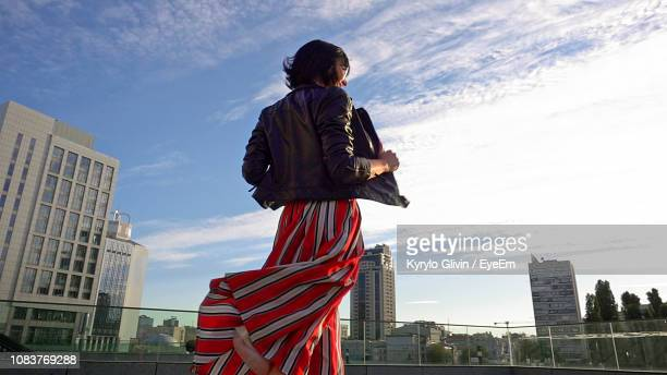 happy woman wearing striped skirt and jacket on footpath in city - スカート ストックフォトと画像