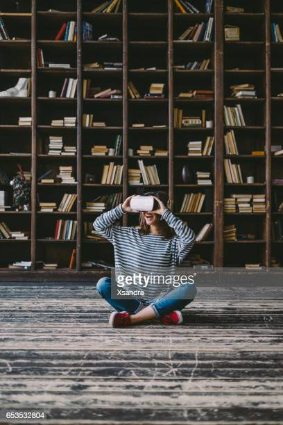 Happy woman wearing VR Glasses in front of bookshelves