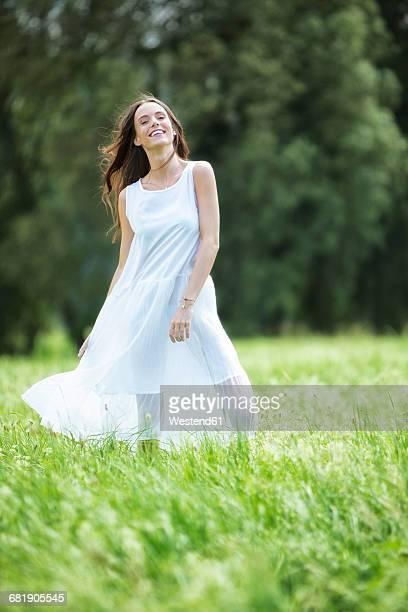 happy woman wearing white summer dress standing on a meadow - サンドレス ストックフォトと画像