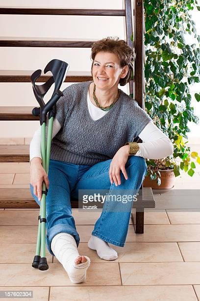 glückliche frau mit einem gebrochenen bein mit krücken - gipsbein stock-fotos und bilder